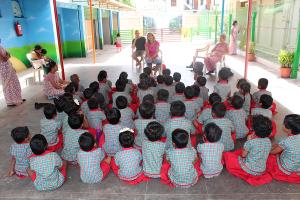 Barna sitter på rad og rekke og er forventningsfulle til hva Læreren fra Norge skal fortelle dem.