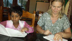 Monica lærer Anbu å brette spå mens vi venter på maten